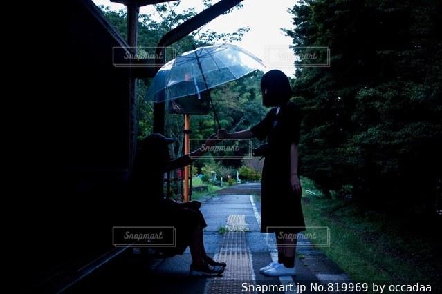傘を持って雨の中に立っている男の人 - No.819969