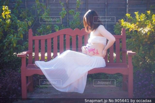 本を読んでベンチに座っている女性の写真・画像素材[905641]
