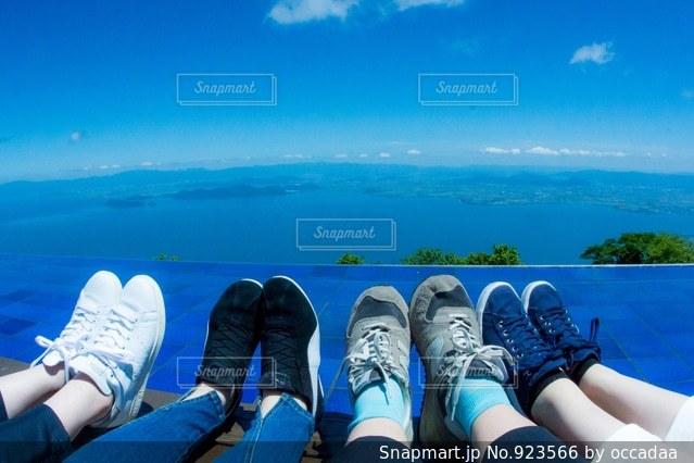 水の体の横に座っている人々 のグループの写真・画像素材[923566]