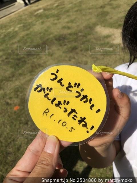 黄色いフリスビーを持つ手の写真・画像素材[2504880]