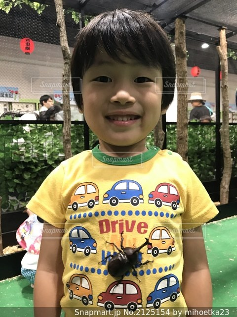 黄色いTシャツの男の子とカブトムシの写真・画像素材[2125154]