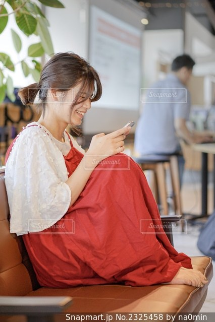 スマホを見る笑顔の女性の写真・画像素材[2325458]