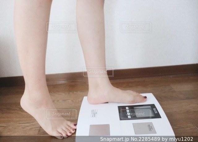 体重計に乗ろうとする女性の写真・画像素材[2285489]