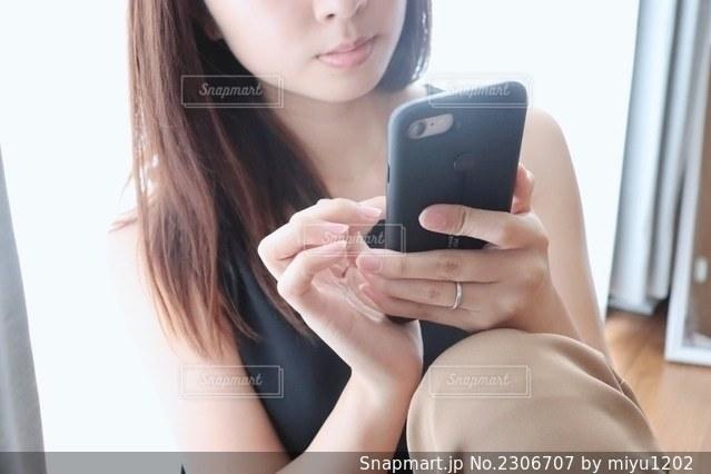 携帯電話を持っている女性の写真・画像素材[2306707]