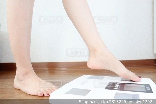 体重計に座っている女性の写真・画像素材[2313229]