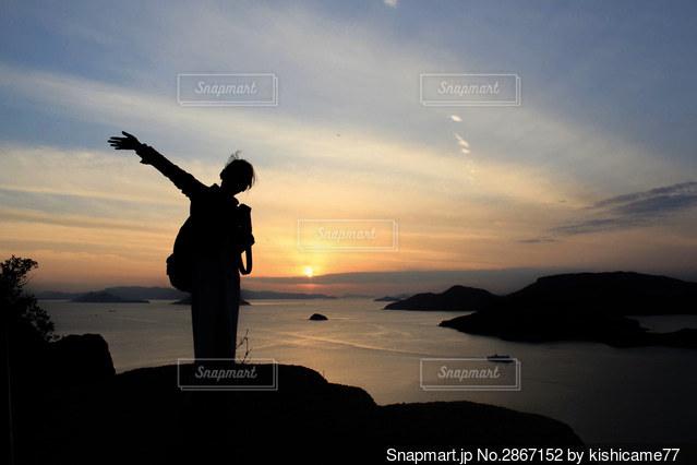 夕焼けの前に立っている人の写真・画像素材[2867152]