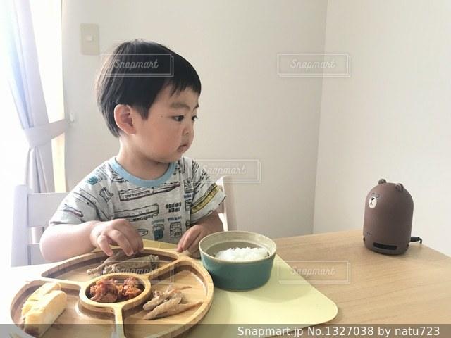 食品のプレートをテーブルに座って若い男の子の写真・画像素材[1327038]