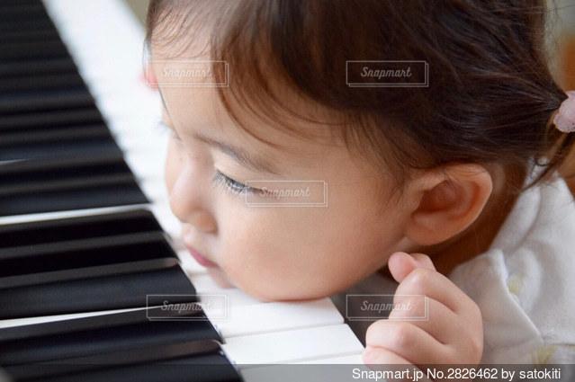 ピアノに座っている小さな女の子の写真・画像素材[2826462]