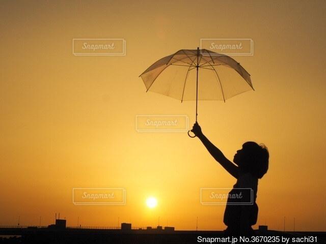 雨の中で夕日を持つ男が傘を持っているの写真・画像素材[3670235]