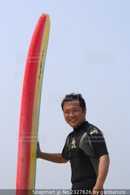 サーフボードを持ちビーチの前にで笑顔の写真・画像素材[2327626]