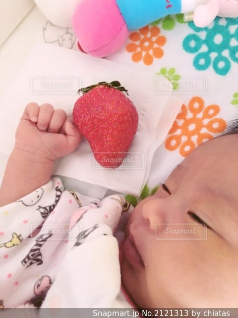 ベッドの上に横たわっている赤ん坊の写真・画像素材[2121313]