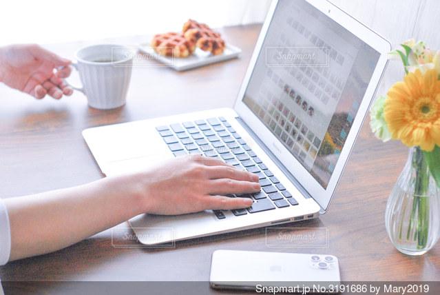 テーブルの上に座っているラップトップコンピュータを使っている人の写真・画像素材[3191686]