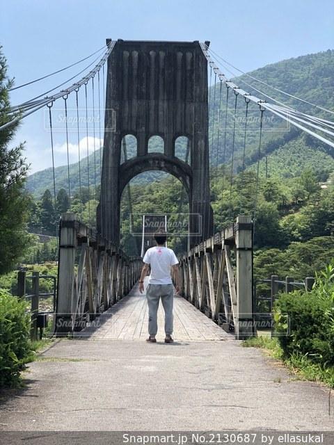 橋を渡って歩いている男の写真・画像素材[2130687]