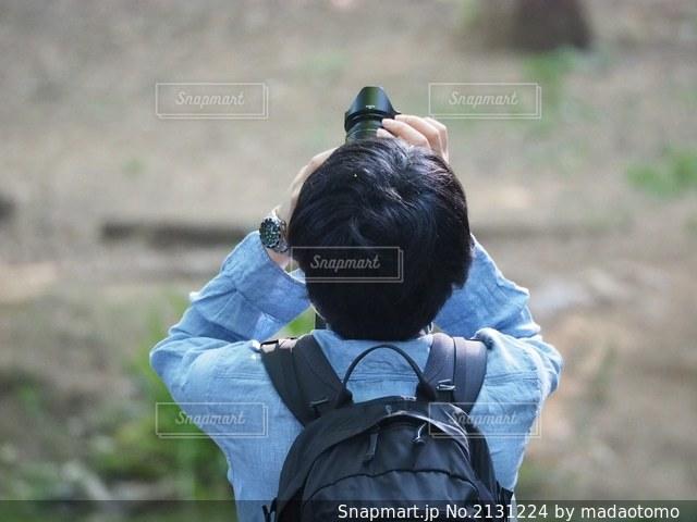 野原に座っている男の写真・画像素材[2131224]