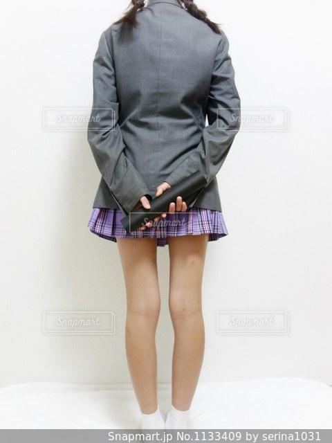 ブレザーの制服を着た女子の後ろ姿全身、両手に卒業証書を持っているの写真・画像素材[1133409]