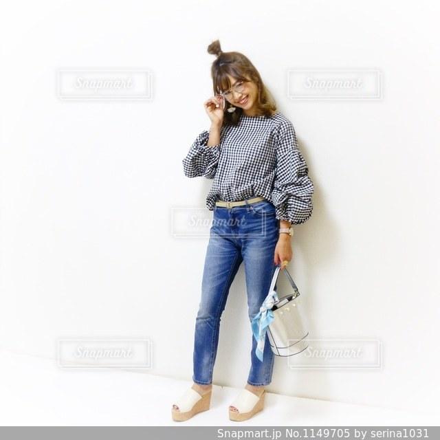 ギンガムチェックにハイウエストデニムを合わせて笑顔てメガネを持つ女性のコーデの写真・画像素材[1149705]