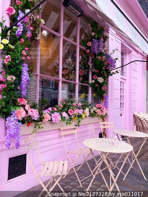 建物の前の椅子にあるピンクの花の写真・画像素材[2127328]