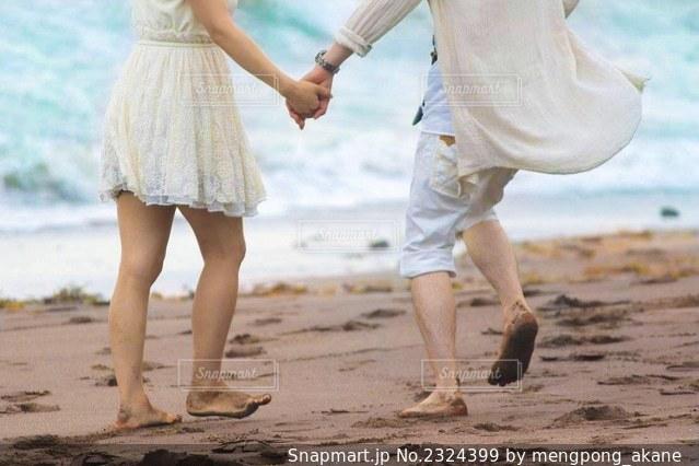 浜辺で手を繋いで歩くカップルの写真・画像素材[2324399]