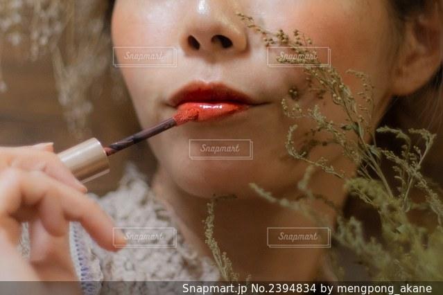 赤いリップグロスを塗っている女性の写真・画像素材[2394834]