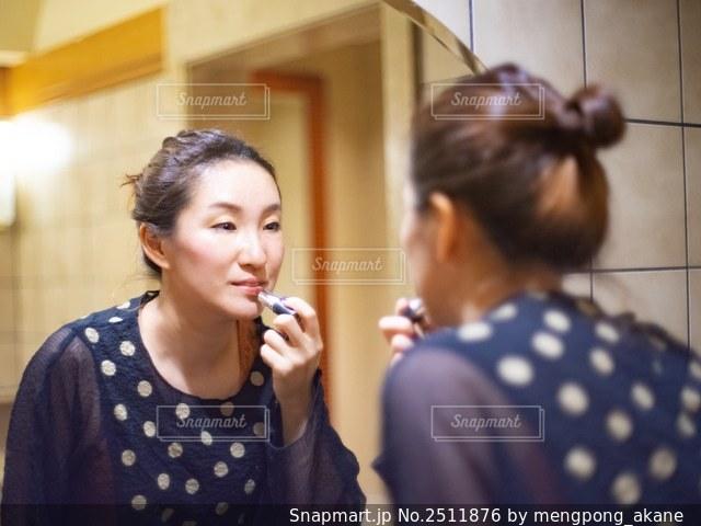 ドレッサーの前で化粧をする女性の写真・画像素材[2511876]