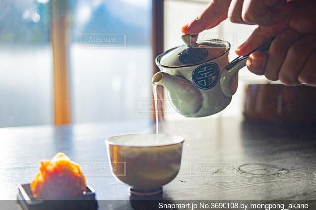 急須でお茶を注ぐ人の手とお茶菓子の写真・画像素材[3690108]