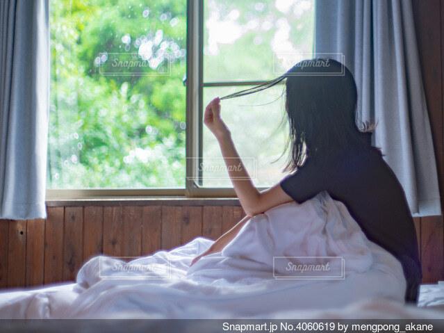 ベッドの上で髪の毛を触る寝起きの女性の写真・画像素材[4060619]