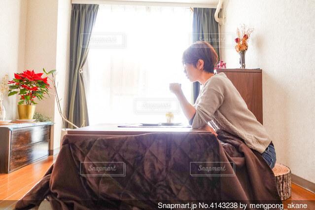 こたつに入りながらコーヒーを飲む人の写真・画像素材[4143238]