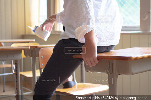 教室の机に座って飲み物を飲んでいる男子校生の写真・画像素材[4648434]