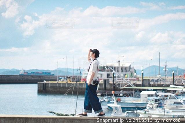 水域の隣に立っている男の写真・画像素材[2416513]
