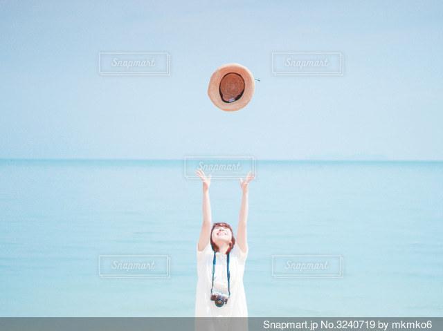 水の体の隣に立っている男の写真・画像素材[3240719]