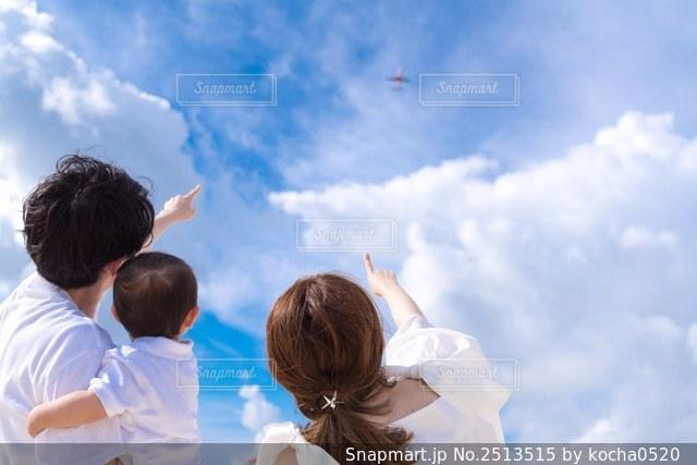 青空と飛行機を見上げる家族の後ろ姿の写真・画像素材[2513515]