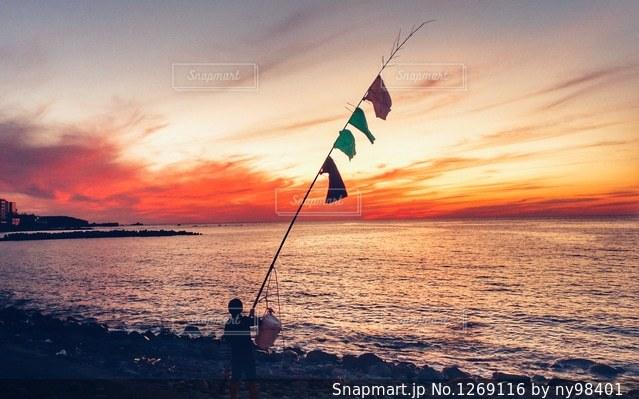 夕陽に竿をかかげる海の写真・画像素材[1269116]