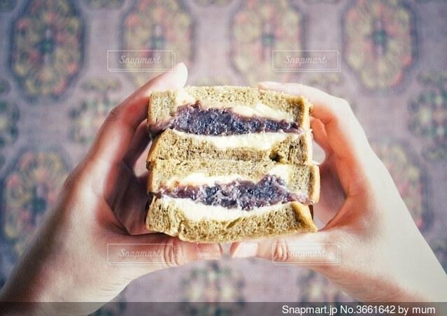 サンドイッチを持つ手の写真・画像素材[3661642]