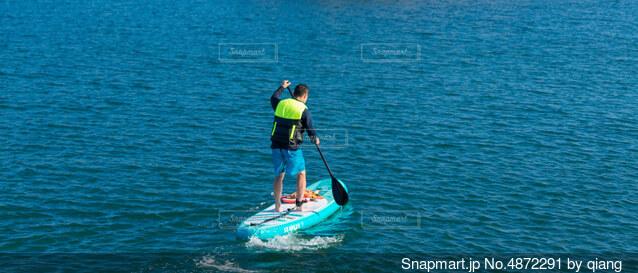 穏やかな海面でサップボードをしている男性の写真・画像素材[4872291]
