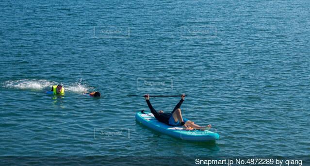 リゾート地の海面でサップボードを遊んでいる親子の写真・画像素材[4872289]