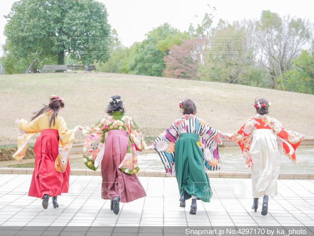 卒業袴を着た女子大生が手を繋ぎ夢に向かって走り出すの写真・画像素材[4297170]
