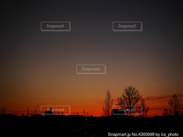 燃えるような赤色の夕焼けと街のシルエットの写真・画像素材[4300699]
