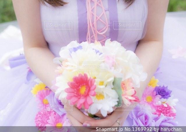 彼女は手に花とテーブルに座っている女性の写真・画像素材[1369792]