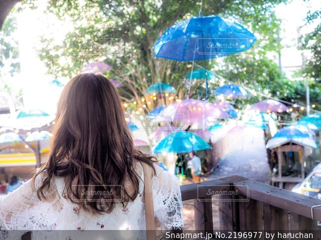 青い傘を持ってテーブルに座っている女性の写真・画像素材[2196977]