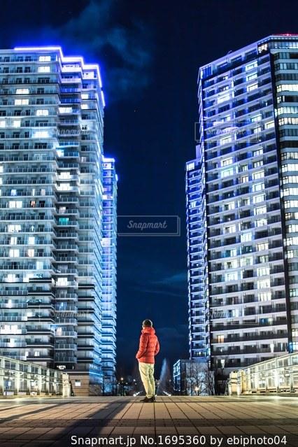 背の高い建物の前に立っている人の写真・画像素材[1695360]