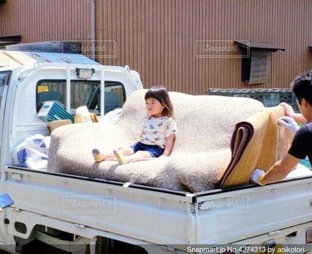 引っ越しのトラックのソファーに座った幼女の写真・画像素材[4274313]
