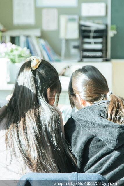 教室の席で話をしている女の子2人の写真・画像素材[4633753]