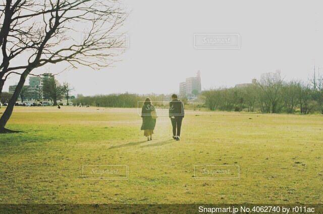 原っぱを歩くカップルの後ろ姿の写真・画像素材[4062740]