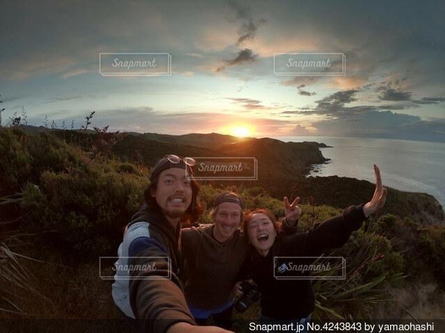 山と海の絶景の夕陽。その前でポーズを取る人たちの写真・画像素材[4243843]