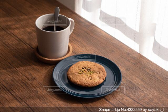 木製のテーブルの上にコーヒーとクッキーの写真・画像素材[4322559]