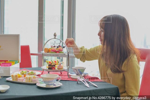 テーブルの上の豪華なスイーツを食べようとする女性の写真・画像素材[4286775]