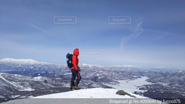 雪に覆われた山の上に立っている男の写真・画像素材[4093040]