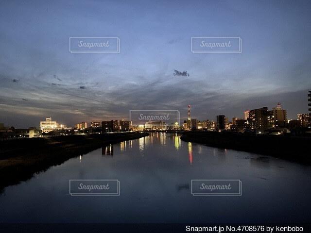 川の水面に夜景が映り、空に浮かんでいるよう。の写真・画像素材[4708576]