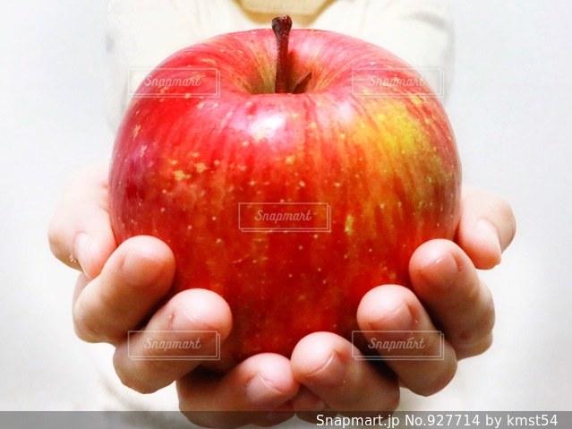リンゴを差し出す手の写真・画像素材[927714]