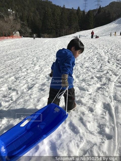 雪をスノーボードに乗る男覆われた斜面の写真・画像素材[950254]